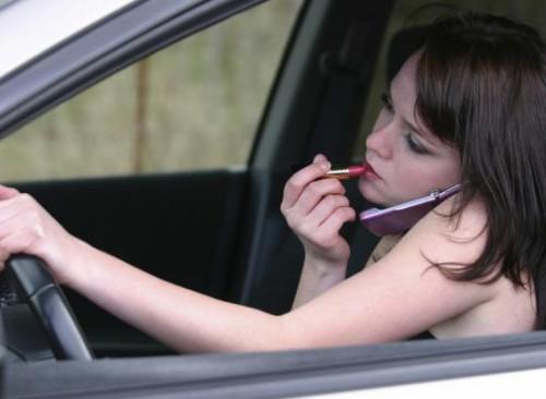 Moteris vairuoja, dažosi ir kalba telefonu